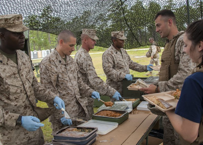 U.S. Marine Corps food service specialists with 1st Battalion, 10th Marine Regiment, 2nd Marine Division serve unitized group rations to Marines and their families during a Jane Wayne Day event aboard Camp Lejeune, N.C., June 6, 2014. The purpose of the event was to give family members a chance to better understand what their loved ones do in the Marine Corps. (U.S. Marine Corps photo by Sgt. Christopher Q. Stone, COMCAM, MCI-East, Camp Lejeune/Released)